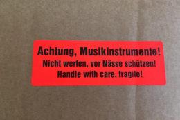 Ein Sticker auf dem Versandkarton mahnt alle unvorsichtigen Postboten der Welt