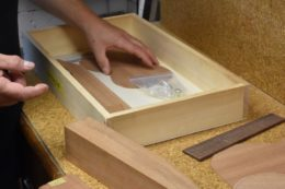 In kleinen Holzschachteln schlummern die Bugle-Ukulelen in spe
